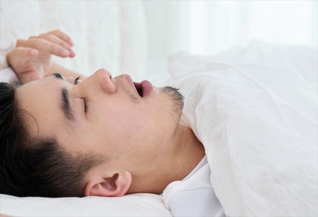 いびきをかいて寝る男性